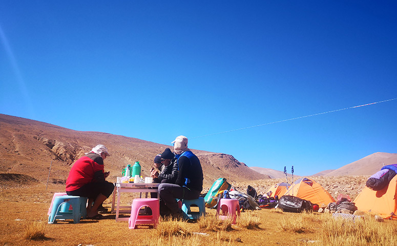 Having the meals besides the camping site during the Tibet trekking trip.