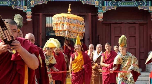 The 11th Panchen Lama is escorted by monks playing religious musical instruments and walks on a yellow carpet symbolizing noble auspiciousness to the Panchen Pagoda in the Xihuang Temple where the clothes of the 6th Panchen Lama was buried. The 11th Panchen Lama Bainqen Erdini Qoigyijabu gives blessings to monks and laymen by conducting a head-touching ritual in the Xihuang Temple of Beijing on May 18.
