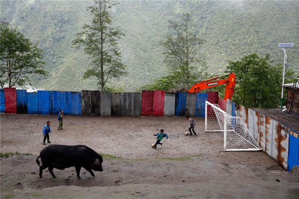 Children play football at school while a hog looks for food at Bangxin Village School in Medog county,Tibet. Although the playground is surrounded by a sheet-metal fence, it is not unusual for children to kick their football off the steep cliff